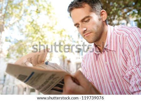 Close up portrait of a senior businessman reading a financial newspaper while sitting in a classic city square. - stock photo