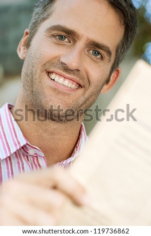 Close up portrait of a senior businessman reading a financial newspaper while sitting in the city. - stock photo