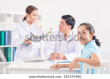 Close-up portrait of a senior patient looking at camera while doctor and nurse discussing on the foreground  - stock photo