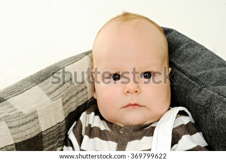 close up portrait of a serious chubby three minth old boy with adorable cheeks looking straight at the camera wearing brown and white shirt