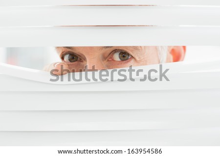 Close-up portrait of a serious mature businessman peeking through blinds in the office