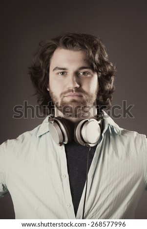 Close up Portrait of a Serious Young Man with Headphone Around his Neck, Looking at the Camera on a Brown Gradient Background.