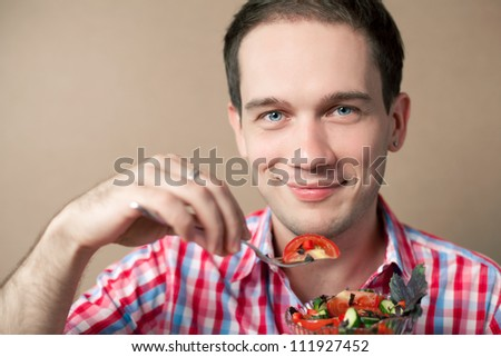 Close-up portrait of a slim handsome boy eating salad over wooden background. studio shot - stock photo