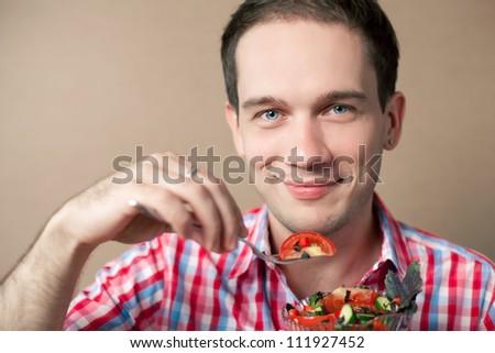 Close-up portrait of a slim handsome boy eating salad over wooden background. studio shot - stock photo