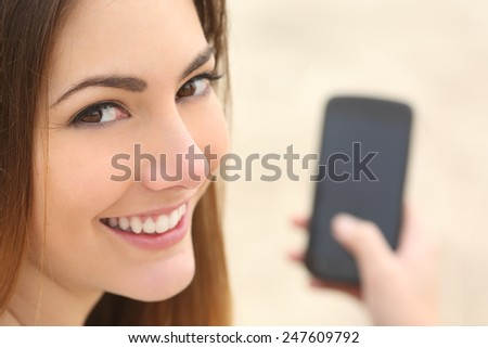 Close up portrait of a smiley woman using a smart phone on the beach - stock photo
