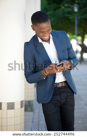 Close up portrait of a smiling african american man sending text message on mobile phone - stock photo