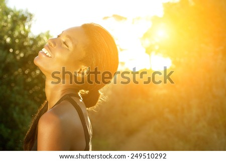 Close up portrait of a smiling african american sports woman standing outdoors - stock photo