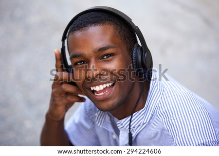 Close up portrait of a smiling african american teen with headphones - stock photo