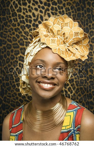 Close-up portrait of a smiling African American woman wearing traditional African clothing in front of a patterned wall. Vertical format. - stock photo