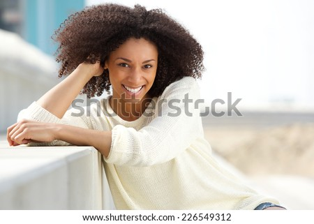 Close up portrait of a smiling african american woman with curly hair sitting outdoors - stock photo