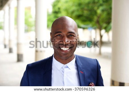 Close up portrait of a smiling african businessman standing outdoors in city - stock photo
