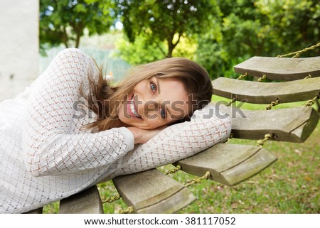 Close up portrait of a smiling attractive woman relaxing on hammock outside - stock photo