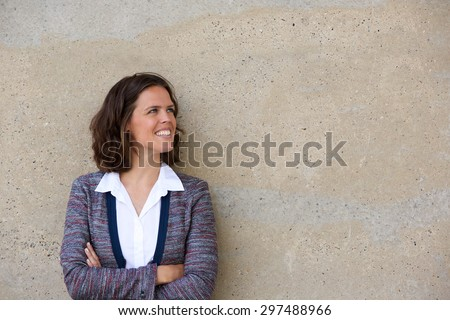 Close up portrait of a smiling business woman standing with arms folded looking away - stock photo