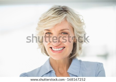 Close-up portrait of a smiling businesswoman against blurred background in office