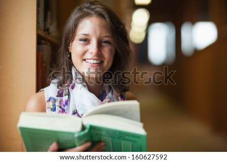 Close-up portrait of a smiling female student in the library - stock photo