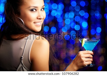 Close-up portrait of a smiling girl holding a cocktail - stock photo