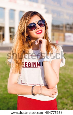 Close-up portrait of a smiling girl with ombre hair holding her left hand near chin. Girl wears white shirt and red skirt. Girl stands in park in the citycenter. She wears black sunglasses. - stock photo