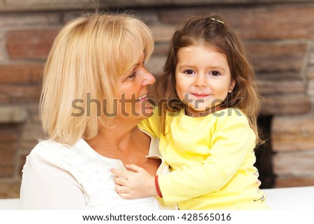Close up portrait of a smiling grandmother and granddaughter embracing, facing each other - stock photo