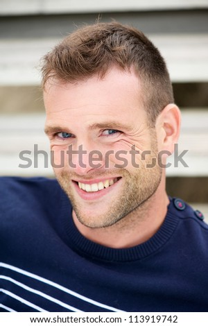 Close up portrait of a smiling handsome young man outdoors - stock photo