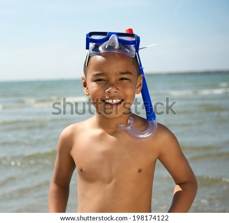 Close up portrait of a smiling little boy with snorkel by the sea - stock photo
