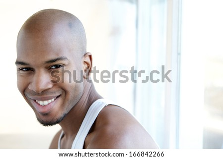 Close up portrait of a smiling man sitting by window