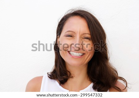 Close up portrait of a smiling mid adult woman posing against white background  - stock photo