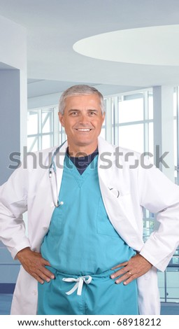 Close up portrait of a smiling middle aged doctor in scrubs with stethoscope around his neck. Vertical format in modern medical facility.