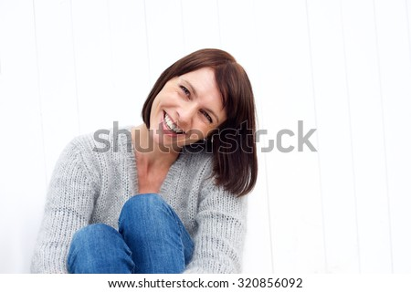 Close up portrait of a smiling middle aged woman sitting against white wall - stock photo