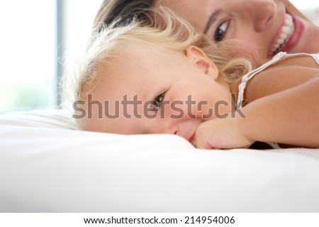 Close up portrait of a smiling mother playing with cute baby girl - stock photo