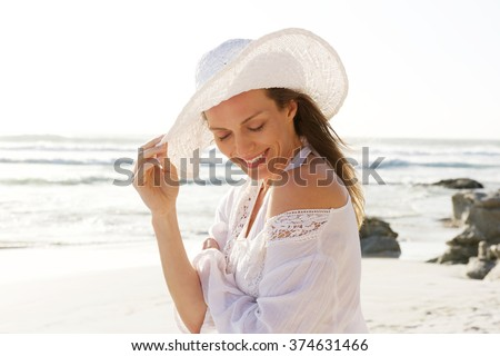 Close up portrait of a smiling older woman with hat at the beach  - stock photo