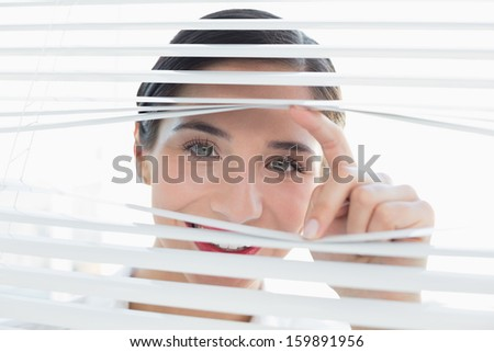 Close-up portrait of a smiling young business woman peeking through blinds