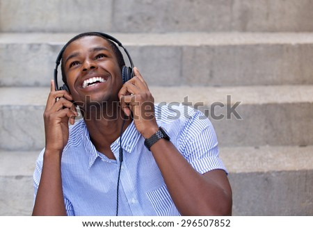 Close up portrait of a smiling young man listening to music on headphones and looking up - stock photo