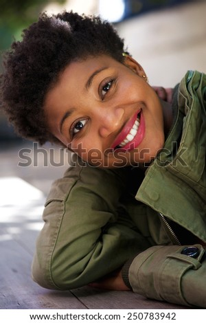 Close up portrait of a smiling young woman sitting outdoors