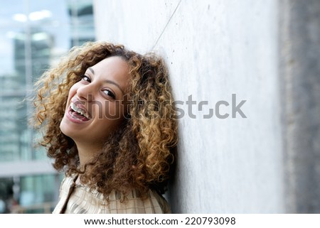 Close up portrait of a smiling young woman with curly hair
