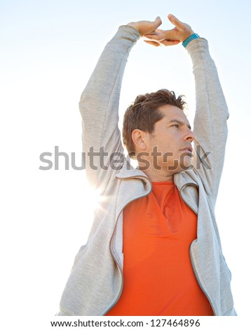 Close up portrait of a sports man stretching his arms up in the air against a sunny blue sky with sun rays filtering through his body. - stock photo