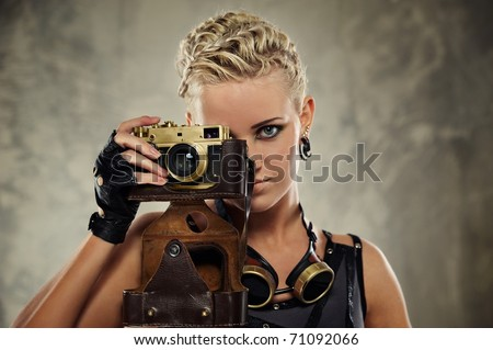 Close-up portrait of a steam punk girl with a photocamera - stock photo