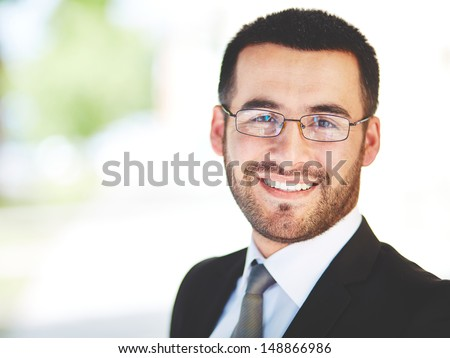 Close-up portrait of a successful businessman looking at camera with smile - stock photo