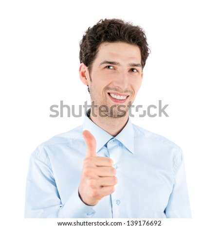 Close-up portrait of a successful handsome businessman who smiles and shows a thumb up gesture to camera. Isolated on white background.