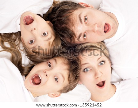 Close-up portrait of a surprised family having fun together lying on a bed at home - top view - stock photo