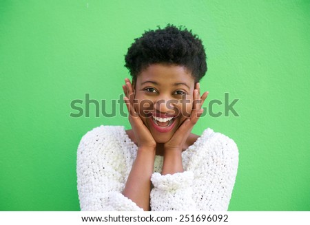 Close up portrait of a surprised young woman smiling with hands on face - stock photo