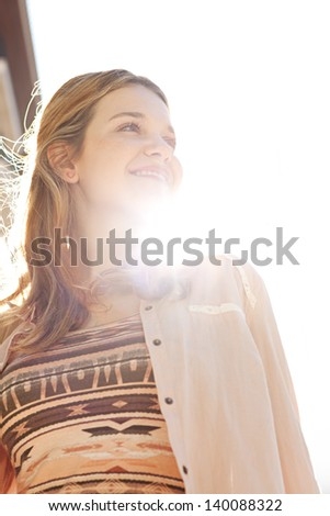 Close up portrait of a teenage girl in a city street during a sunny day, looking away from the camera and smiling against the sky with sun rays filtering through her neck. - stock photo