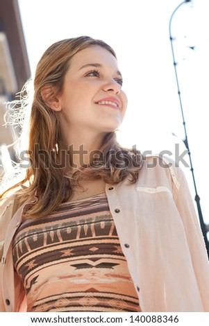 Close up portrait of a teenage girl in a city street during a sunny day, looking away from the camera and smiling against the sky. - stock photo
