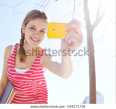 Close up portrait of a teenager girl using her smartphone to take pictures while in the city during a sunny day, smiling at the camera and having fun.