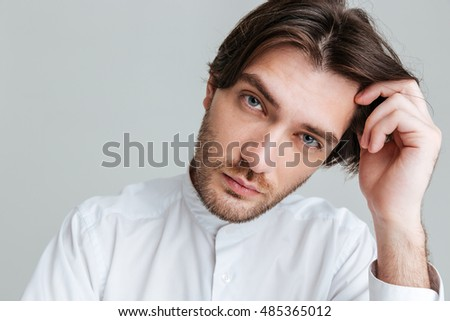 Close up portrait of a thoughtful young brunette man in white shirt sitting at the table isolated on the gray background