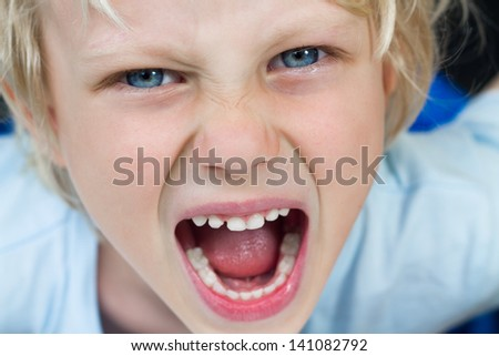 Close-up portrait of a very angry screaming boy. - stock photo