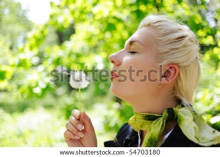 Close-up portrait of a woman blowing to dandelion flower
