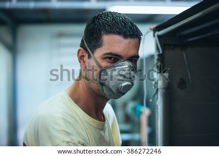 Close up portrait of a worker with protective mask against dust and fumes. His job is metal and aluminum painting and protection with paintbrush. - stock photo