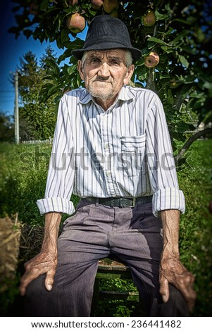 Close-up portrait of a wrinkled and expressive old farmer seated near an apple tree in the yard. - stock photo
