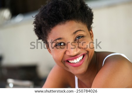 Close up portrait of a young african american woman laughing - stock photo
