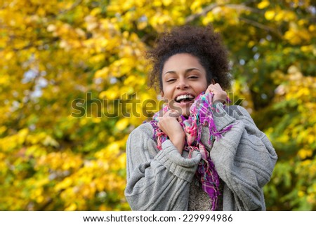 Close up portrait of a young african american woman smiling with sweater and scarf in autumn - stock photo